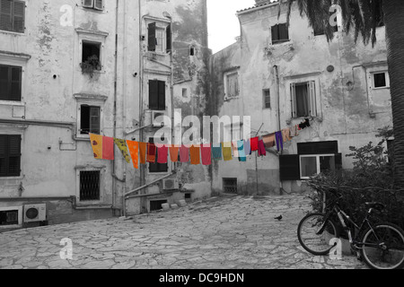 Colourful washing hanging on a washing line on a black and white photograph of the back streets in Corfu Town in - Stock Photo