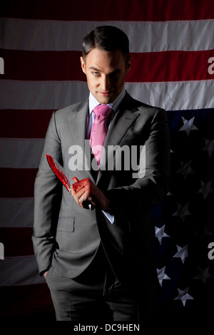 A sharply dressed man holding a bloody knife standing in front of an American flag, posed by model. - Stock Photo