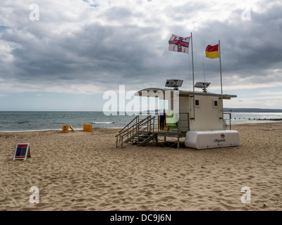 Flags fly over the life-guard's hut on the empty beach at Bournemouth, Dorset - Stock Photo