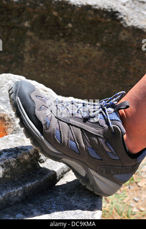 Woman wearing Merrell walking boots placed against part of a ruined column in  Ancient Olympia Peloponnese Greece - Stock Photo