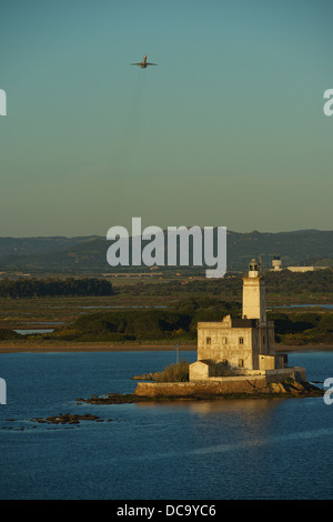 Approaching the Port of Olbia with the ferry boat. Lighthouse of Olbia with airplane taking off from the airport - Stock Photo