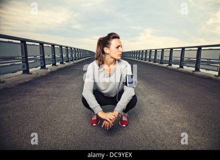 Female runner sitting on the bridge after running - Stock Photo