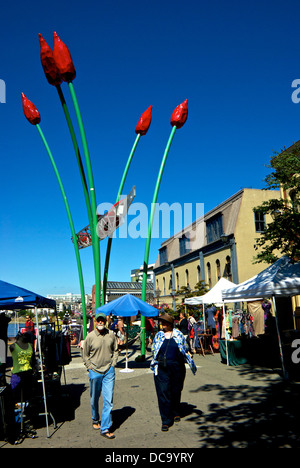 Tourists vendor tents wares under tulip canoe art sculpture Bastion Square summer farmer's market Victoria BC Canada - Stock Photo