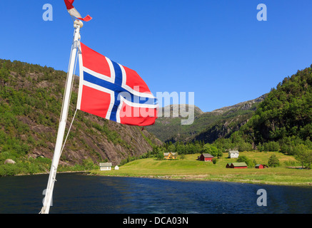 Norwegian flag flying on a boat cruise sailing from Mostraumen into Romarheimsfjorden and Osterfjorden at Mostraum, - Stock Photo