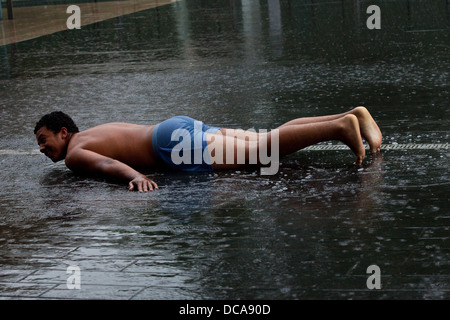 A Young Man Laying On The Pavement In The Rain, The South Bank, London, England - Stock Photo