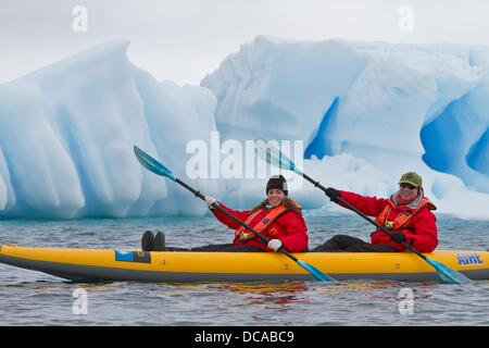 Guests from the Lindblad Expedition ship National Geographic Explorer enjoy Dorian Bay in Antarctica by kayak - Stock Photo
