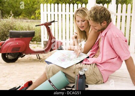 Happy couple on a country trip looking up in a map - Stock Photo