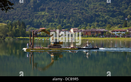 Mechanical Digger being transported on raft via a Tug Boat, Lake Idro, Italy - Stock Photo