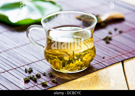 Oolong Tea in a glass by some rolled tea leaves - Stock Photo