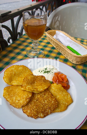 Local cuisine savory pancakes with salmon and kvass beverage in restaurant Vilnius Lithuania Europe - Stock Photo