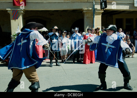 Dressed as Musketeers, young men mock duel in Lupiac, D'Artagnan's birthplace, during a fête honoring the Gascon - Stock Photo