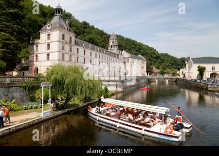 A tourist boat tour on the River Dronne moors at the 7th century Benedictine Abbey, Brantome, the Dordogne, France - Stock Photo