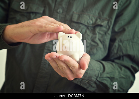 Hand cuddles white piggy coin bank with scared look in its eyes. - Stock Photo