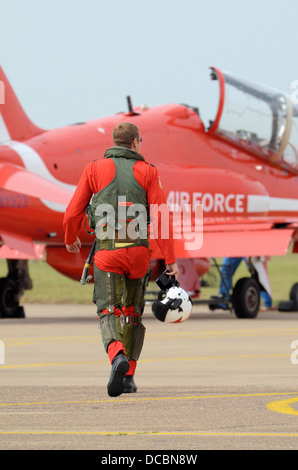 A Red Arrows pilot walks out to his Hawk jet to carry out a display with the team. He's wearing a G-suit over his - Stock Photo