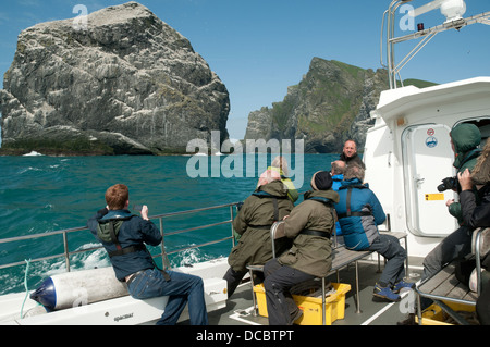 Tourist boat approaching Stac Lee and Boreray, St Kilda archipelago, Outer Hebrides, Scotland, UK. - Stock Photo
