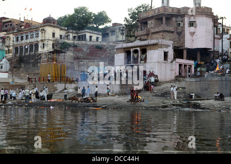Mourners gather at the burning ghats on the banks of the RIver Ganges, Varanasi. - Stock Photo