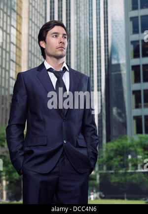 Portrait of a young businessman in a suit standing in city downtown with office buildings in the background. Toronto, - Stock Photo