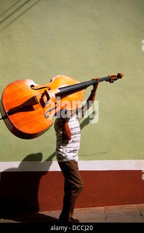 A bass player carrying his double bass. Trinidad de Cuba. Cuba - Stock Photo