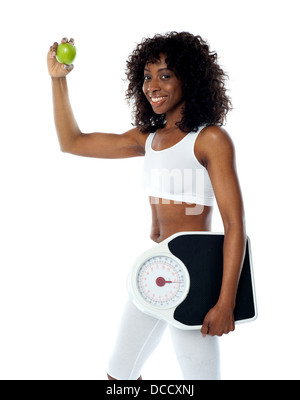 Athlete holding green apple and weighing machine wearing white sport outfit - Stock Photo