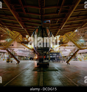 A Boeing 747 is surrounded by gantries during late night work by engineering staff perform maintenance checks in - Stock Photo