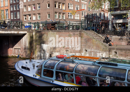 Cruise boat on Korte Prinsengracht canal and buildings on Haarlemmerstraat in Amsterdam, Holland, Netherlands. - Stock Photo