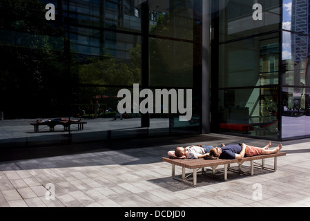 Two men sleep in summer sunshine, sharing a bench in the pedestrian area of Spitalfields in central London. - Stock Photo