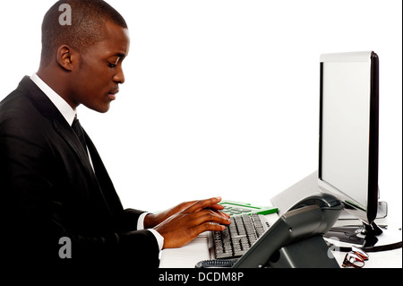 Side view male secretary typing on keyboard working on computer - Stock Photo