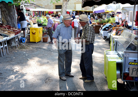 Two Old men in conversation at Cazals market in the Lot Region or Department of South West France - Stock Photo