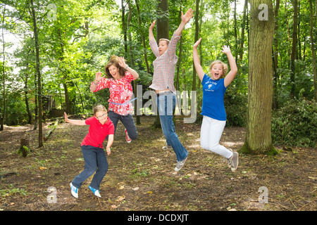 family jumping up in the air outdoors - Stock Photo