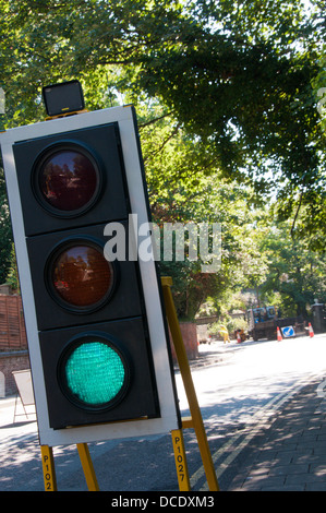 Temporary traffic lights at roadworks showing a green light. - Stock Photo