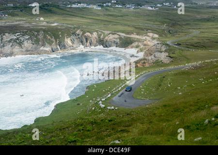 Atlantic Drive car on scenic coastal road with beach and dramatic rough sea Near Dooega Achill Island County Mayo - Stock Photo