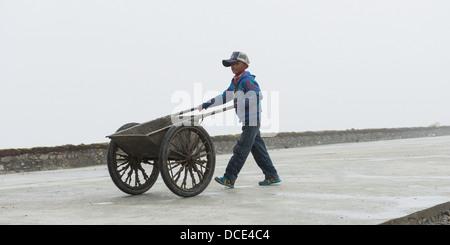 China, Xizang, Tibet, Shannan, Boy pushing two-wheeled cart down walkway - Stock Photo