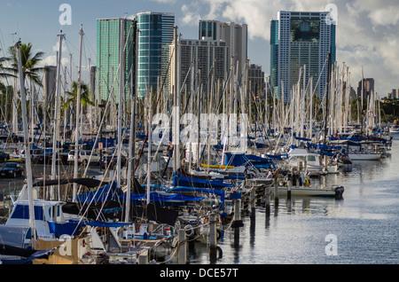 USA, Hawaii, Oahu, Honolulu. Docked Sailboats in Ala Wai Harbor below downtown Honolulu cityscape. - Stock Photo