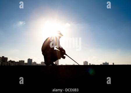 Havana, Cuba; Silhouette Of Man Stooping In Field - Stock Photo