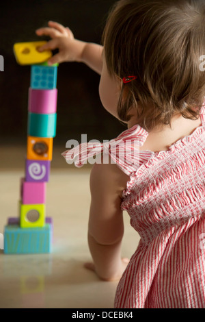 Baby girl skillfully balancing wooden blocks - Stock Photo