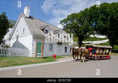 Michigan, Mackinac Island. Traditional horse carriage in front of the American Fur Company Store, Registered Historic - Stock Photo
