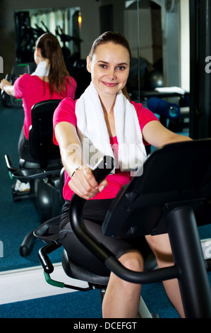 Woman working out in gym with towel around her neck - Stock Photo
