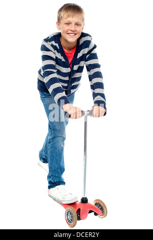 Smart looking kid riding on his zippy cycle. Causal random shot - Stock Photo