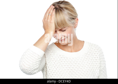 Sad middle aged woman suffering from headache. Placing her hand on forehead. - Stock Photo