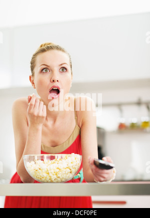 Surprised young woman eating popcorn and watching tv in kitchen - Stock Photo