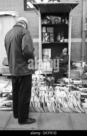 Man selling books at Panjiayuan Flea Market, Beijing, China. - Stock Photo