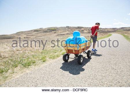 Little boy pulling cart full of balloons - Stock Photo