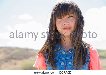 Portrait of cute little girl standing outdoors - Stock Photo