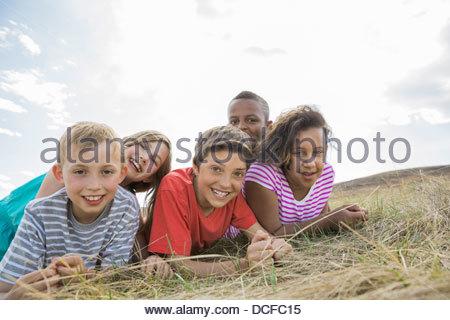 Portrait of playful schoolchildren lying on field - Stock Photo