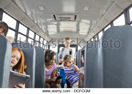 Kids riding on school bus - Stock Photo