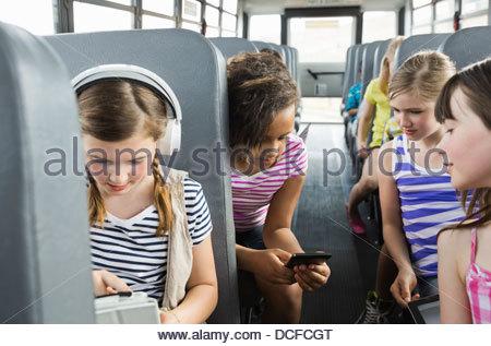 Schoolgirls using smart devices on school bus - Stock Photo
