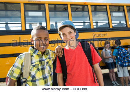 Portrait of schoolboys standing in front of bus - Stock Photo