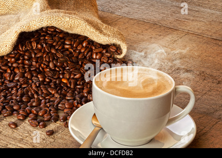 Coffee and Sack of Coffee Beans - a cup of hot steaming espresso coffee on a rustic plank background, with a sack - Stock Photo