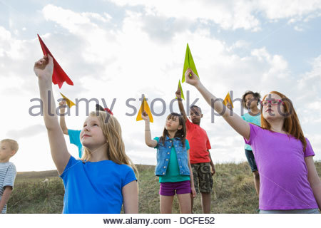 Schoolchildren aiming paper airplanes on field - Stock Photo