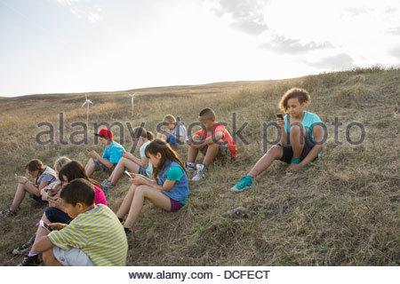 Schoolchildren sitting on hillside using mobile phones - Stock Photo